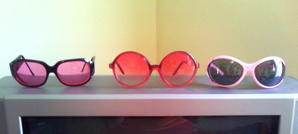 Color photograph of 3 pairs of variously colorful sunglasses atop a TV set.