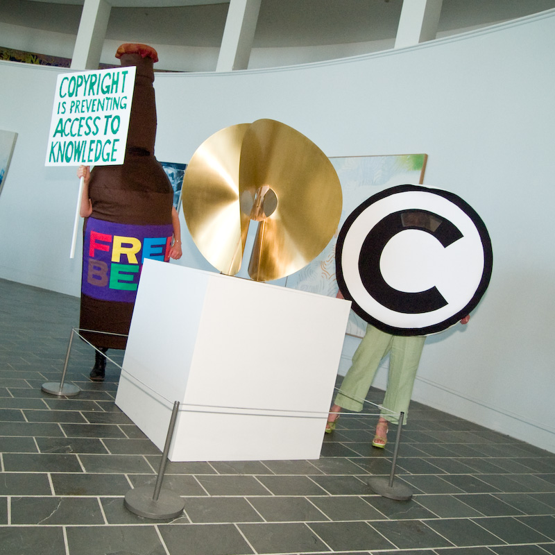 Photograph of an art installation featuring performers wearing costumes of a beer bottle with a FREE BEER label, a DC, and the Creative Commons symbol. The beer bottle is carrying a sign that reads, Copyright is preventing access to knowledge.