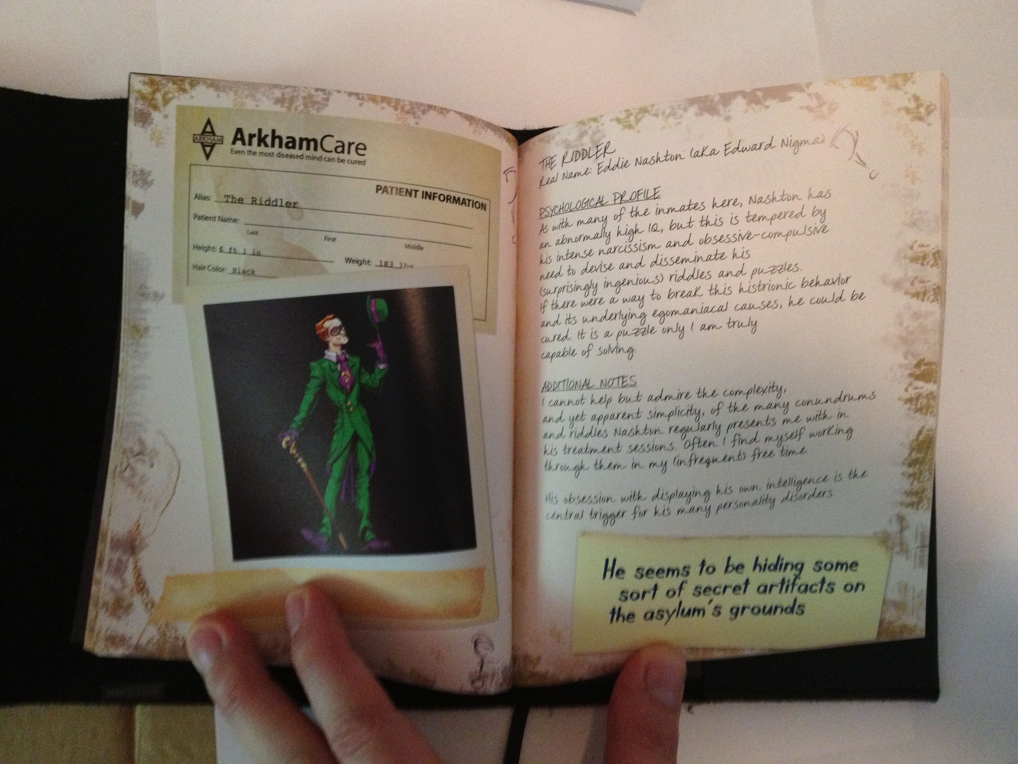 Color image of a tabletop with a white man's hand a book open to two pages describing the Riddler, with a color Polaroid image of a green suit-clad Riddler, the image apparently taped in with masking tape; a yellow sticky note that reads, He seems to be hiding some sort of secret artifacts on the asylum's grounds; and smudged page edges, perhaps indicating mold or wet damage.