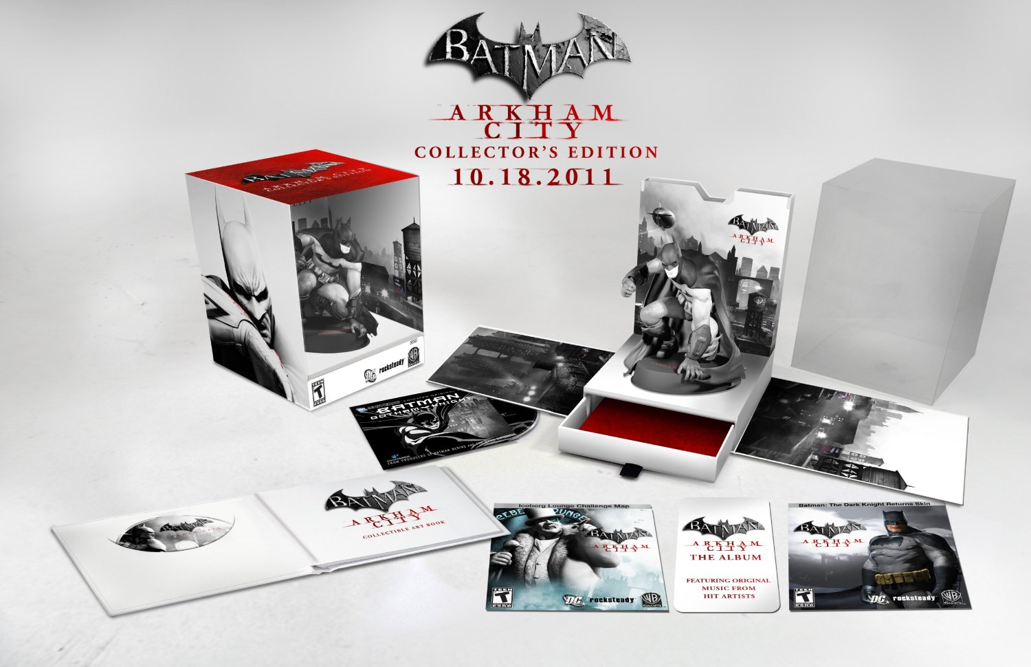 Color image with shades of black, gray, and red predominant, showing the Batman: Arkham City—Collector's Edition boxed up on the left, and disassembled into its components on the right and underneath. Text above reads BATMAN (inside a bat shape), ARKHAM CITY COLLECTOR'S EDITION 10.18.2011.