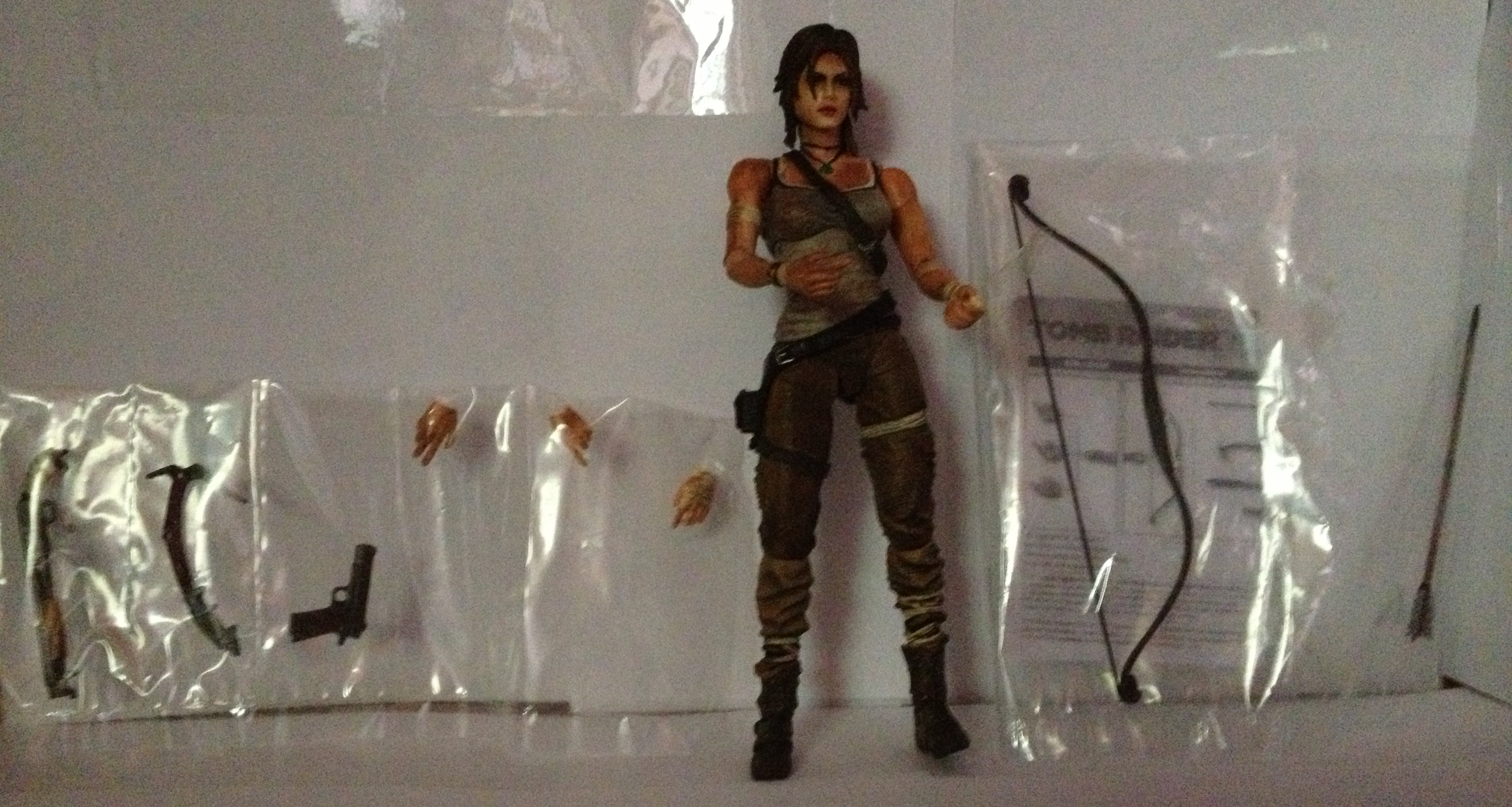 Color image of Lara Croft action figure set against a white wall, with plastic bags containing various artifacts arranged behind it, including weapons, three hands with different shapes, a bow, and an arrow. In with the bow is a black-and-white leaflet with drawings illustrating the components; the words TOMB RAIDER are discernible at the top of the page.