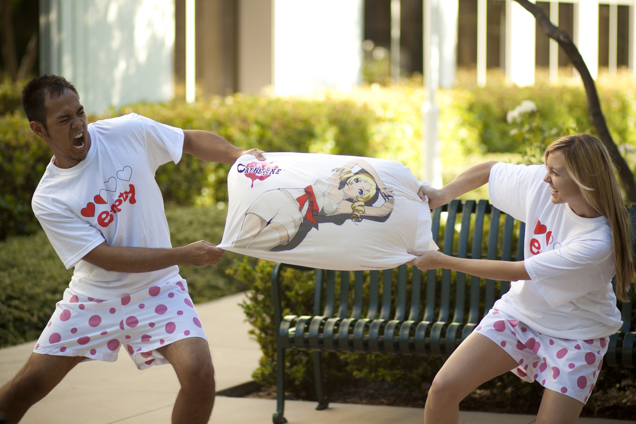 Color image of a black man and a long-haired blonde white woman playing tug-of-war with a Catherine pillow on a sidewalk in front of a green metal park bench. Both are wearing 'Empty Hearts' T-shirts and pink polka-dot boxers.