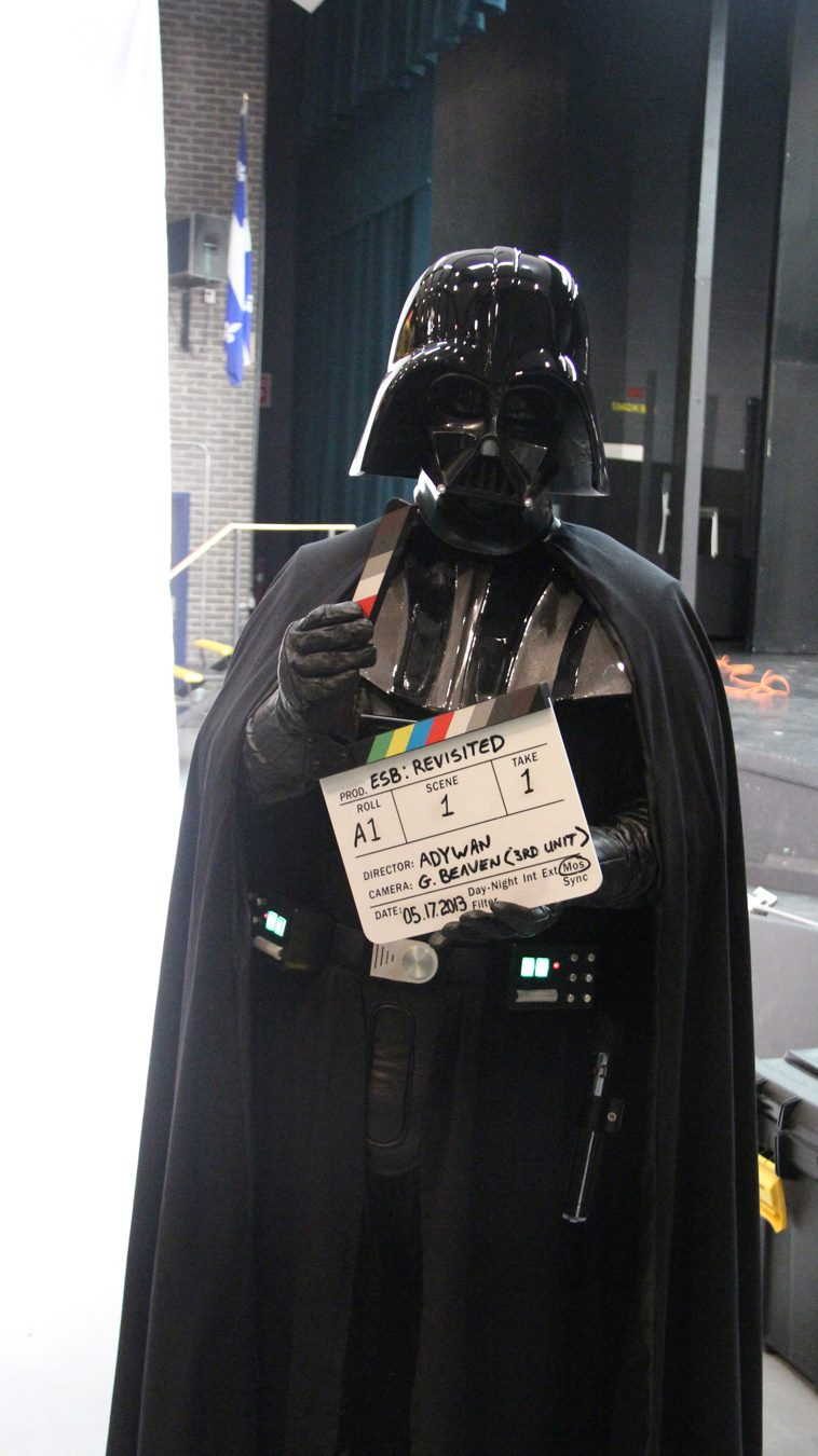 Color photo of person dressed as Darth Vader holding a film slate.