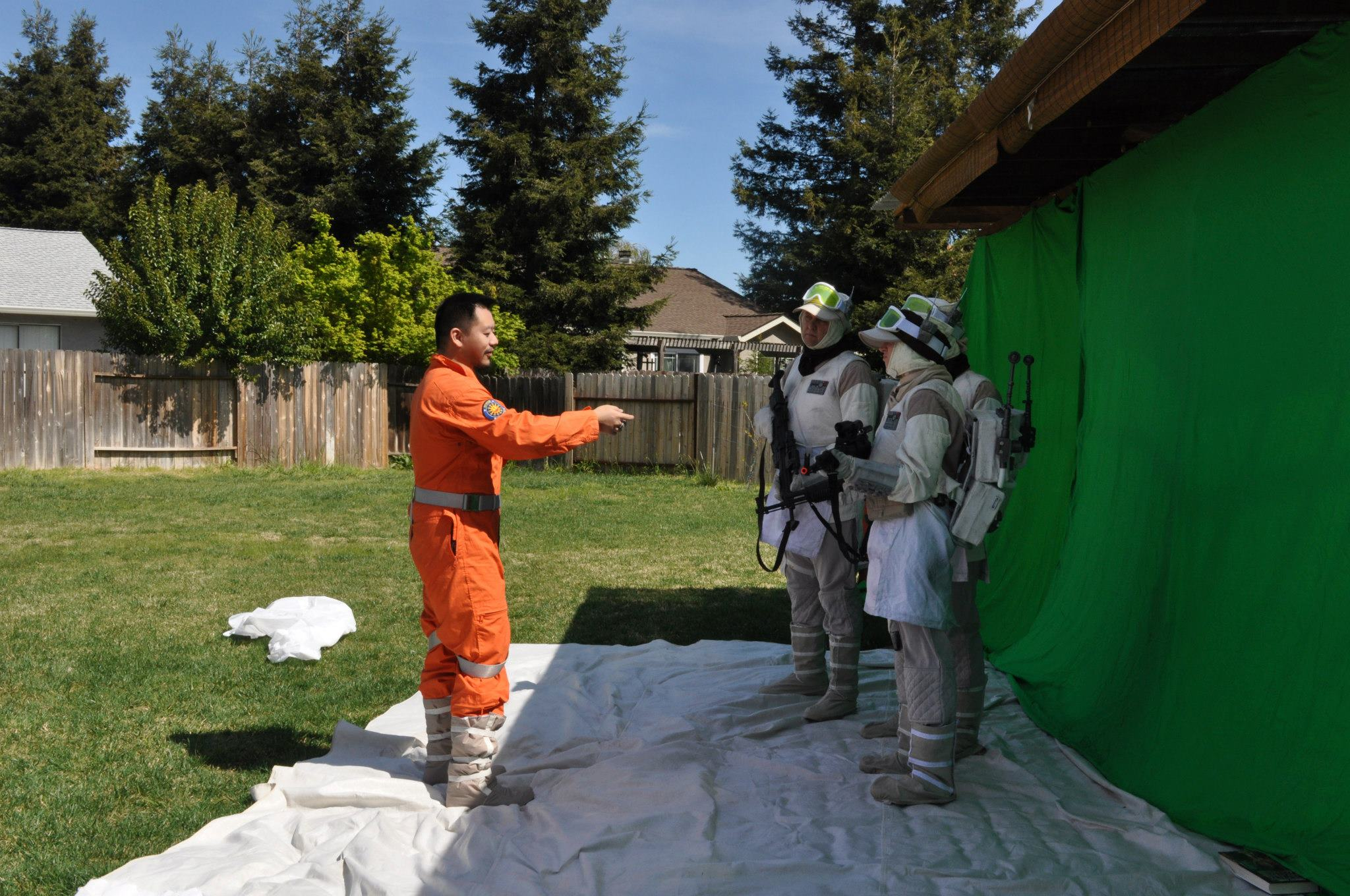 Color photo of man in orange jumpsuit directing two men dressed in rebel soldier uniforms standing in front of a green screen in a backyard.