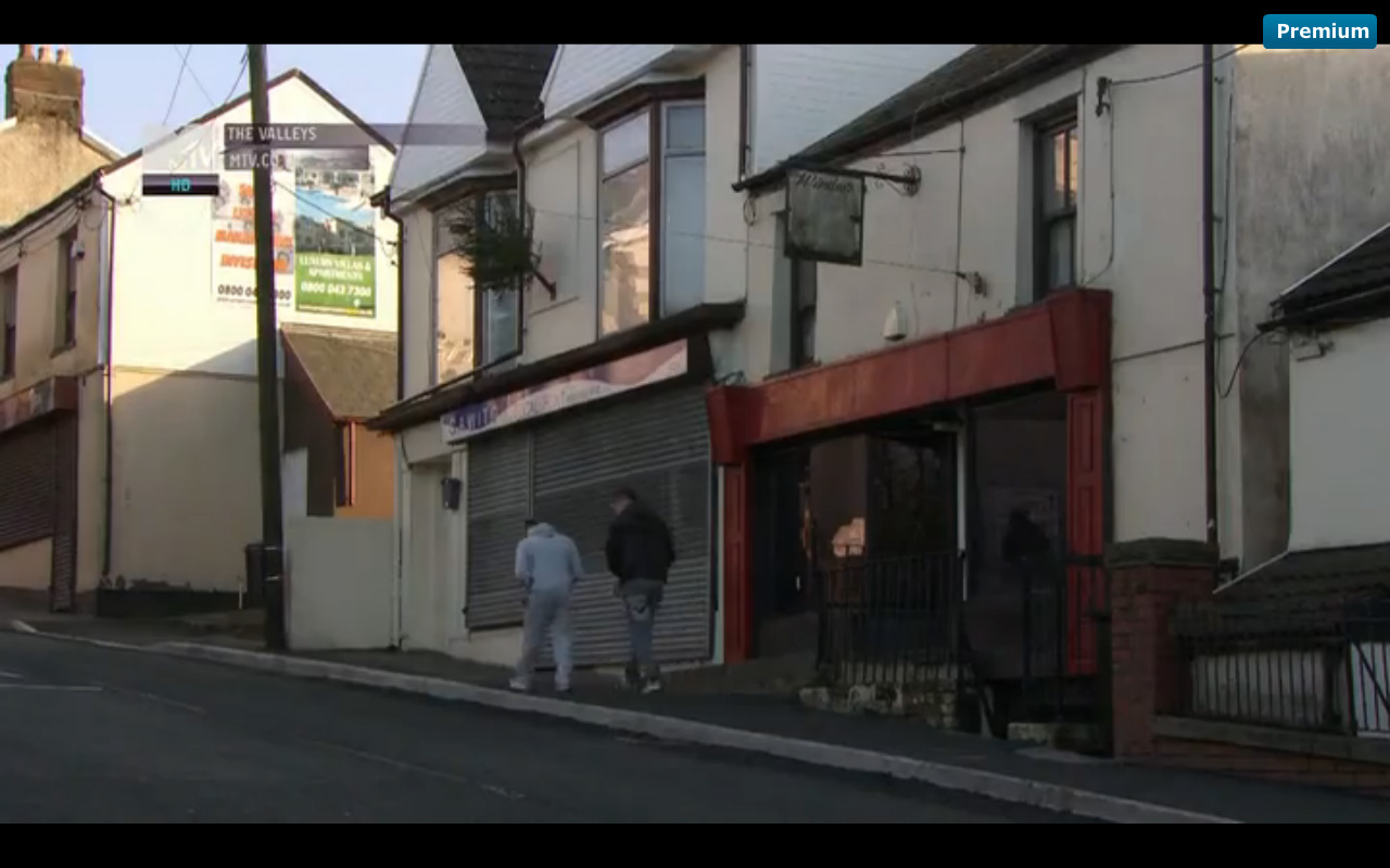 Screenshot of a street scene, with two men, one white and one with his head down, walking beside boarded-up shops.