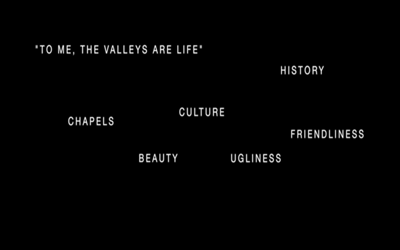 A black rectangle with all-caps white words scattered randomly on the screen. The words read: 'To me, the Valleys are life'; history; chapels; culture; beauty; ugliness; friendliness.