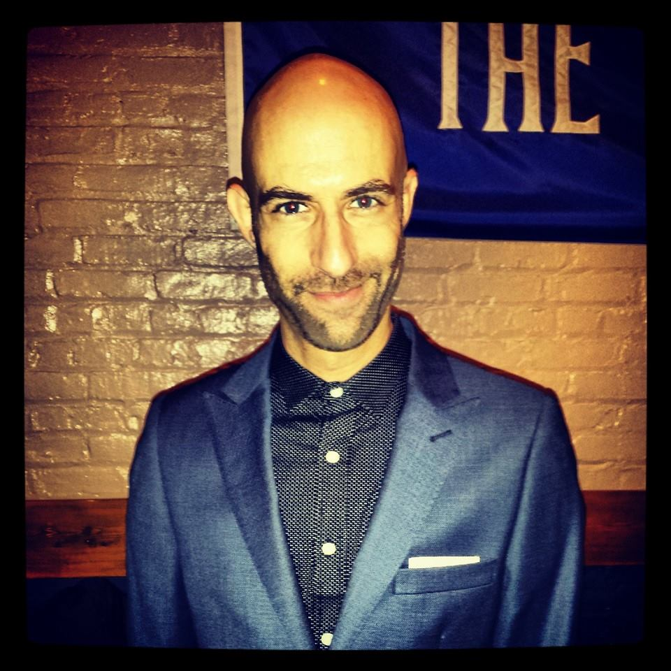 Color photo of bald white man with heavy eyebrows and stubble wearing a checked button-down shirt under a blue blazer.