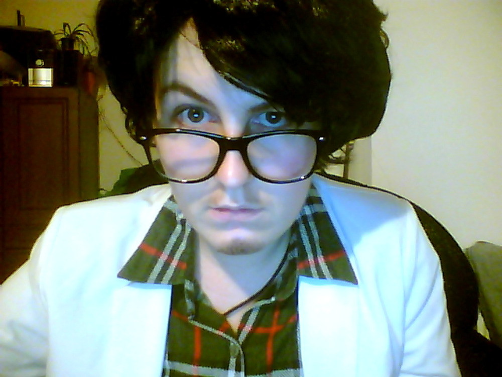 Color photo of a white man wearing a poofy black wig and large black-framed glasses, a green, red, and white-striped button-down shirt, and a white lab coat, staring directly into the camera.