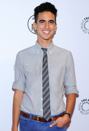Photo of smiling young Hispanic man with dark hair, one hand in a pocket, wearing light gray button-down shirt, a striped gray tie, and jeans.