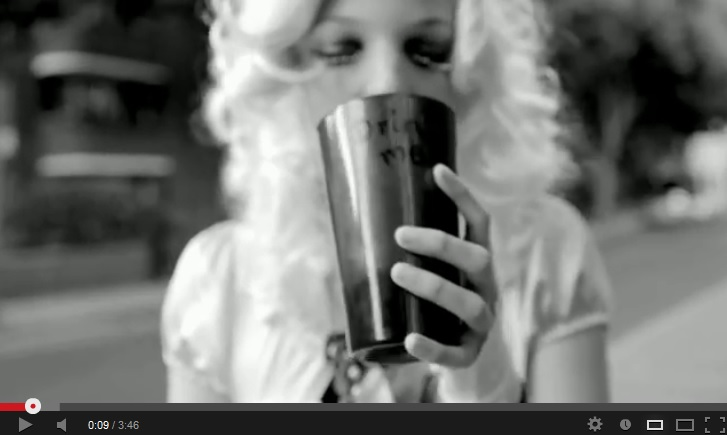 Black-and-white image of an out-of-focus blonde woman, eyes closed, raising an opaque glass/cup reading 'drink me' to her lips. The glass/cup is in focus.