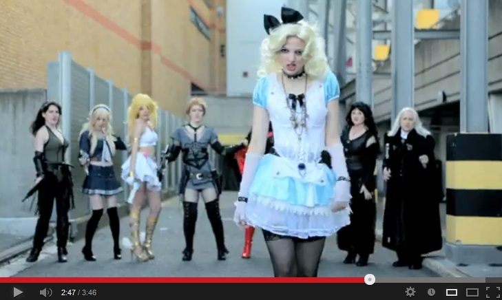 Color image of a sexy blonde woman (Alice) with a big black bow in her hair, standing in the foreground wearing a blue-and-white short dress and black thigh-high semisheer stockings. Behind her is a row of women dressed in various cosplay costumes.