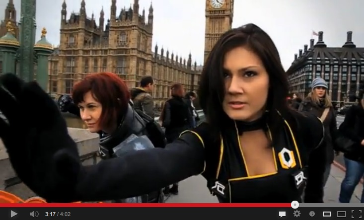 Color image with two women in the foreground, standing in London in front of the Palace of Westminster, one staring straight into the camera, black-gloved arm extended.