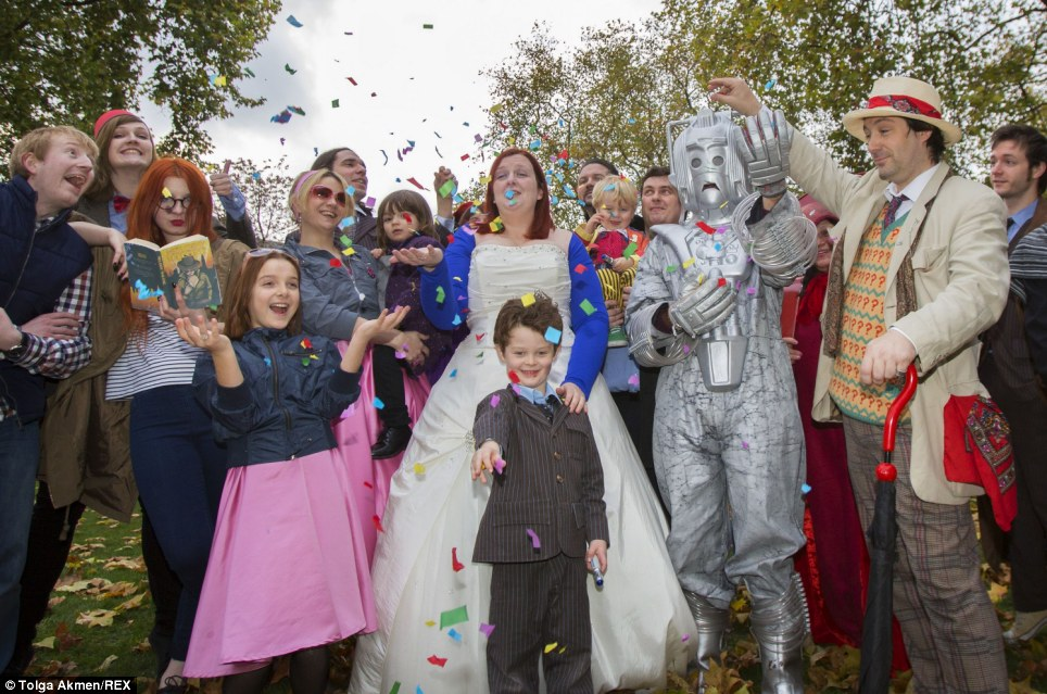 Color photograph taken outdoors of a bride, a Cyberman, a man dressed as the Seventh Doctor, and a child dressed as the Tenth Doctor, as well as well-wishers, with confetti flying.