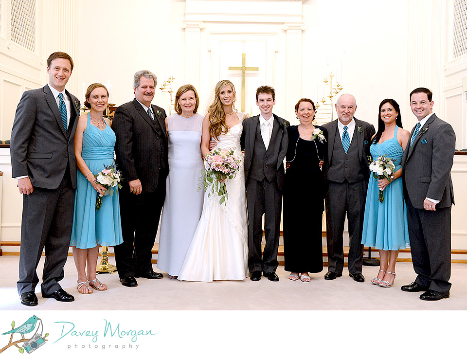 Formal color wedding portrait of ten people dressed traditionally, standing in a church in front of a Christian cross.