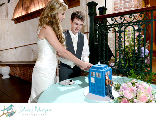 Color photo of a bride and groom cutting into a blue TARDIS cake.