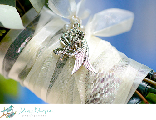 Color close-up photograph of a white ribbon wrapped around flower stems, with a silver charm of a rose and angel wings.