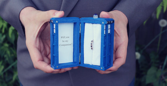 Color photograph of a man's hands holding open a rectangular TARDIS box with a ring set with four gemstones inside. Text to left (inside the cover) reads, 'Will you be my companion?'