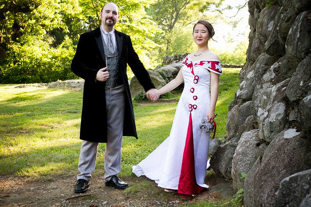 Color photograph of a man and a woman standing outside by a tree, holding hands. The man wears a frock coat, cravat, and waistcoat. The woman wears a white dress with a train, decorated with touches of red; she holds a bouquet bound by a red ribbon.
