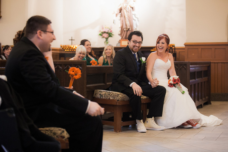 Color candid photograph of people sitting in pews in a Christian church. The bride and groom are both wearing Converse shoes (his white, hers red), but otherwise they are dressed traditionally, with the groom in a suit and the bride in a sleeveless long white gown.