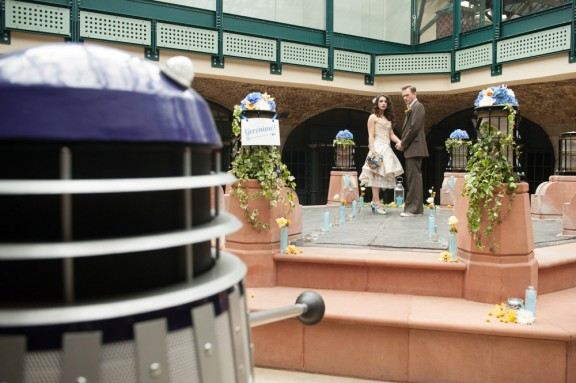 Color image taken in a hotel atrium of a Dalek approaching a bride and groom.
