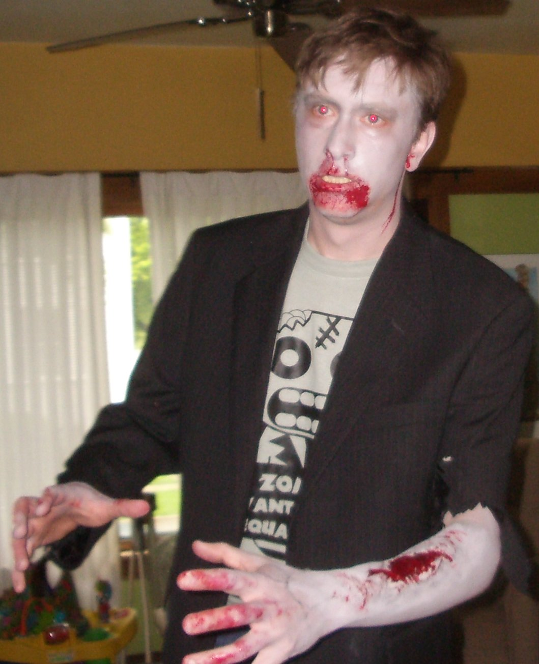 Color photo of a zombie with bloody hands, mouth, and ears.