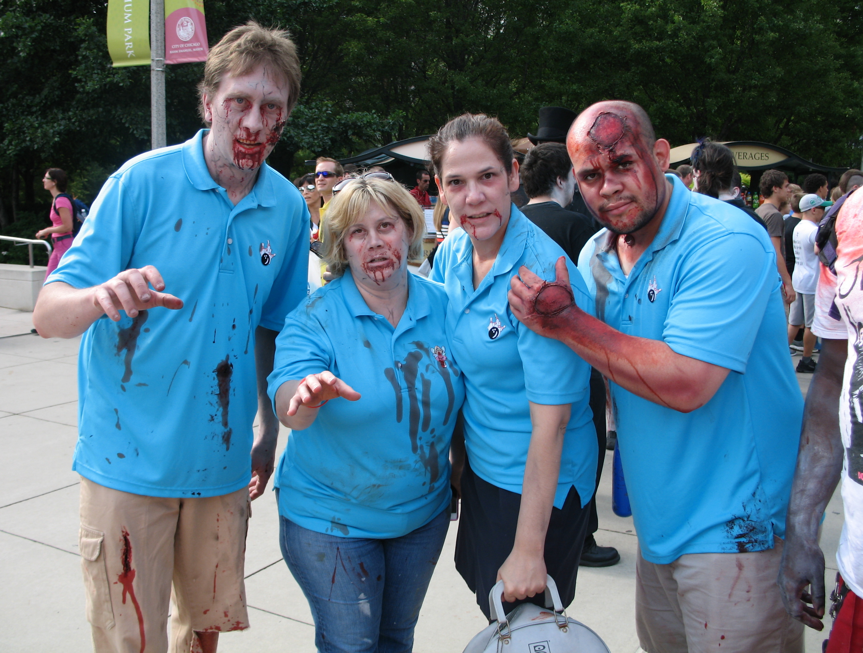 Color photo taken outdoors of four zombies, two men and two women, wearing matching blue shirts. One of the women is holding a bowling ball bag.