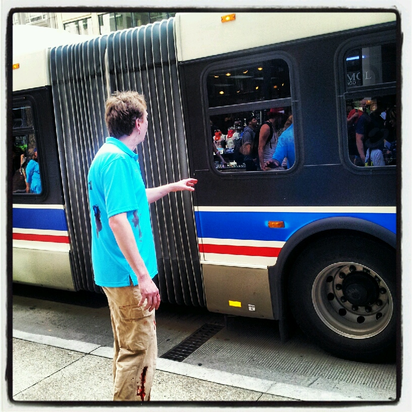 Color image taken outdoors of zombie staring at a municipal bus, one hand extended.