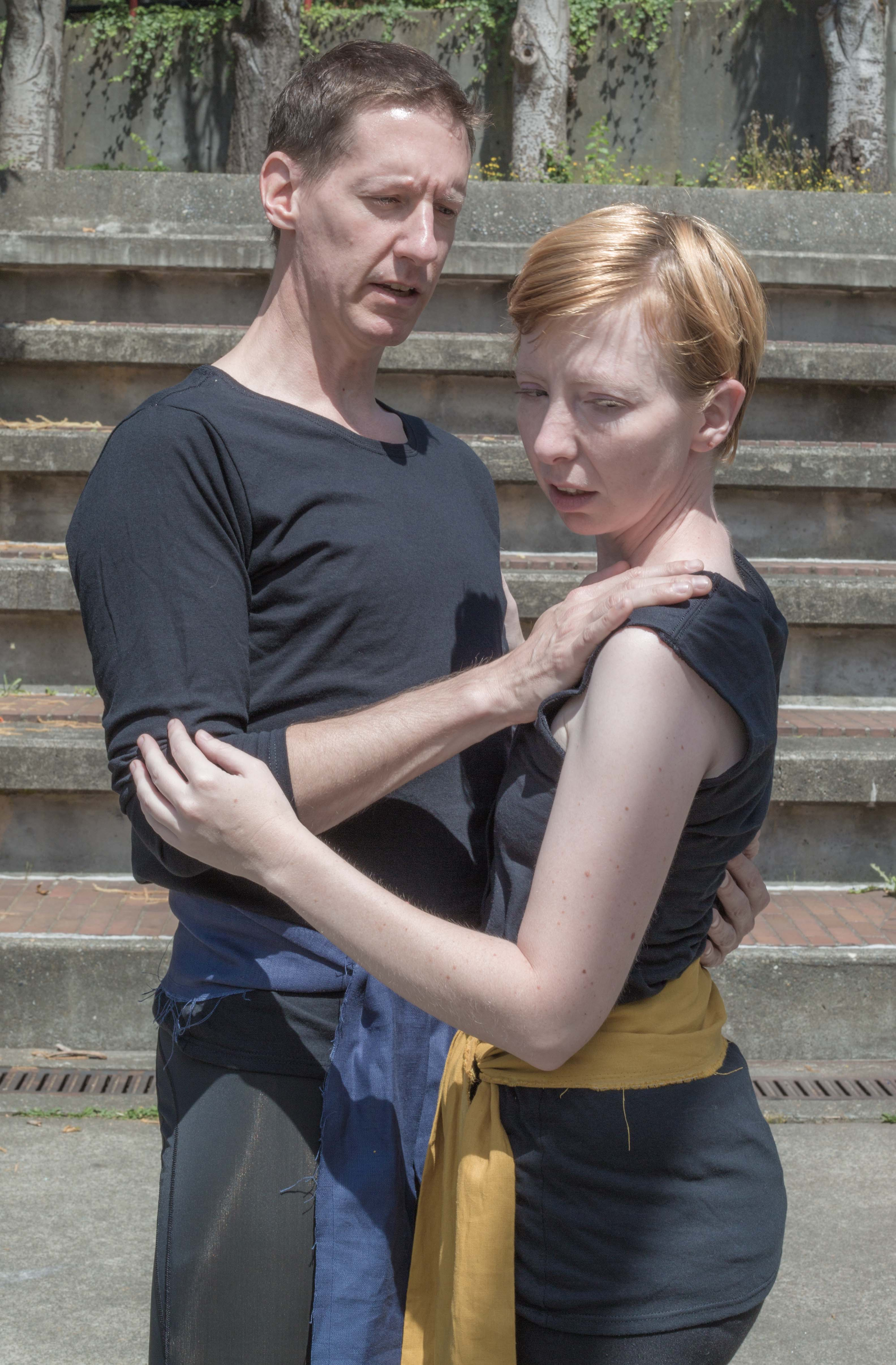 Color photograph of a taller man and a shorter woman, both wearing black, standing outside in a semiembrace, with the woman looking away and down. The woman is wearing a yellow sash to indicate the rank of captain.