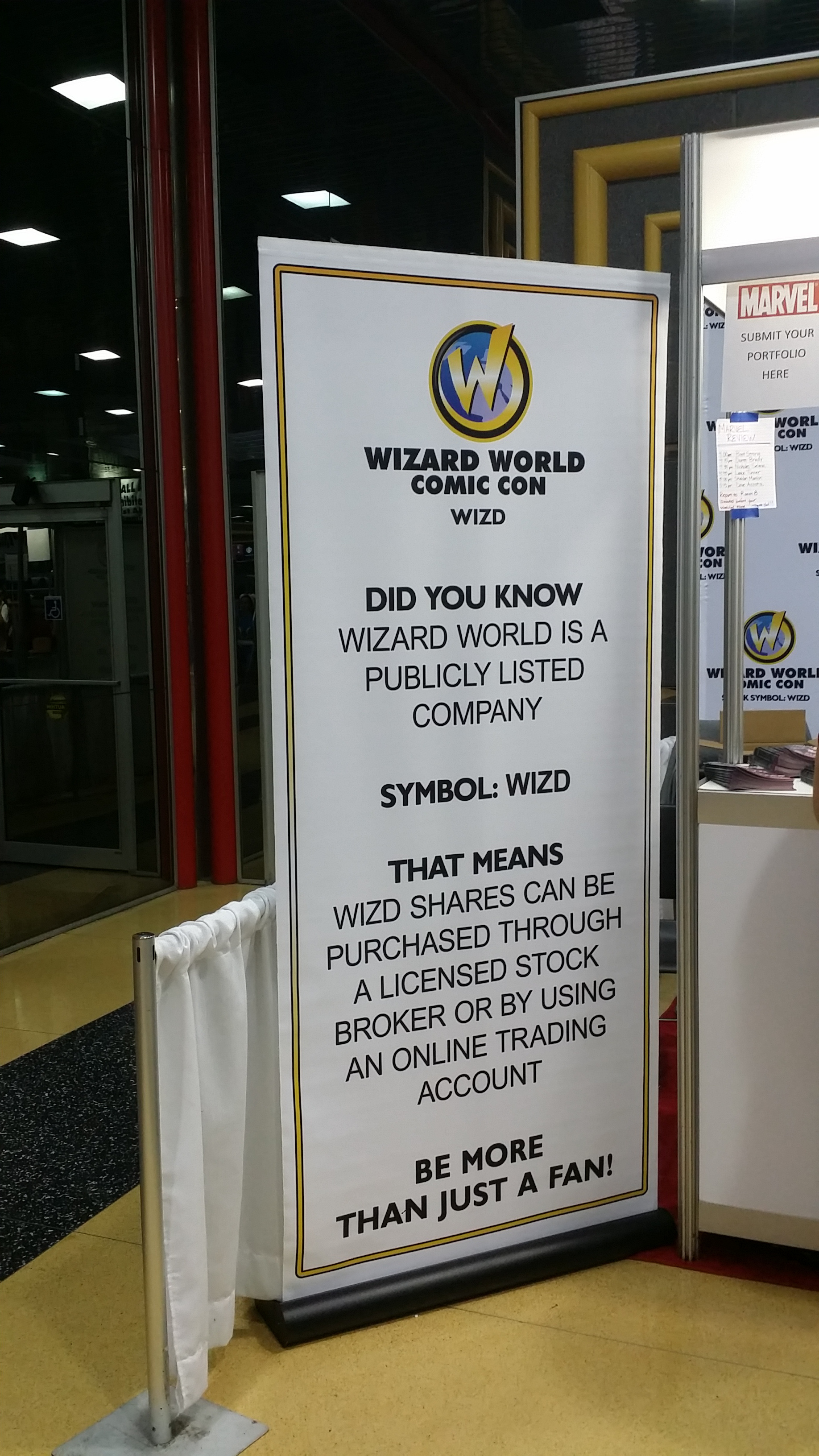 Color photo of a sign up next to a convention booth that reads, in all caps, under the con's logo, 'Wizard World Comic Con. WIZD. Did you know Wizard World is a publicly listed company. Symbol: WIZD. That means WIZD shares can be purchased through a licensed stock broker or by using an online trading account. Be more than just a fan!'