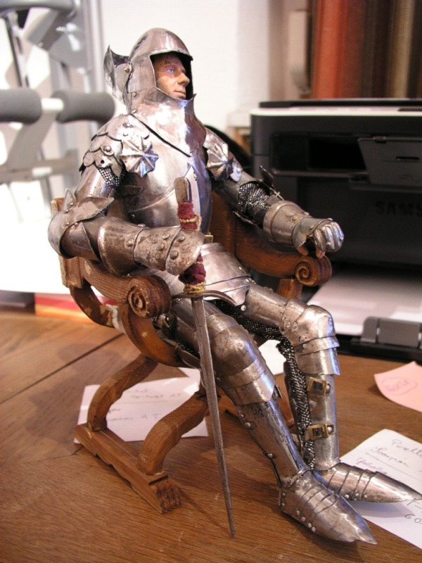 A knight in armor in a chair.