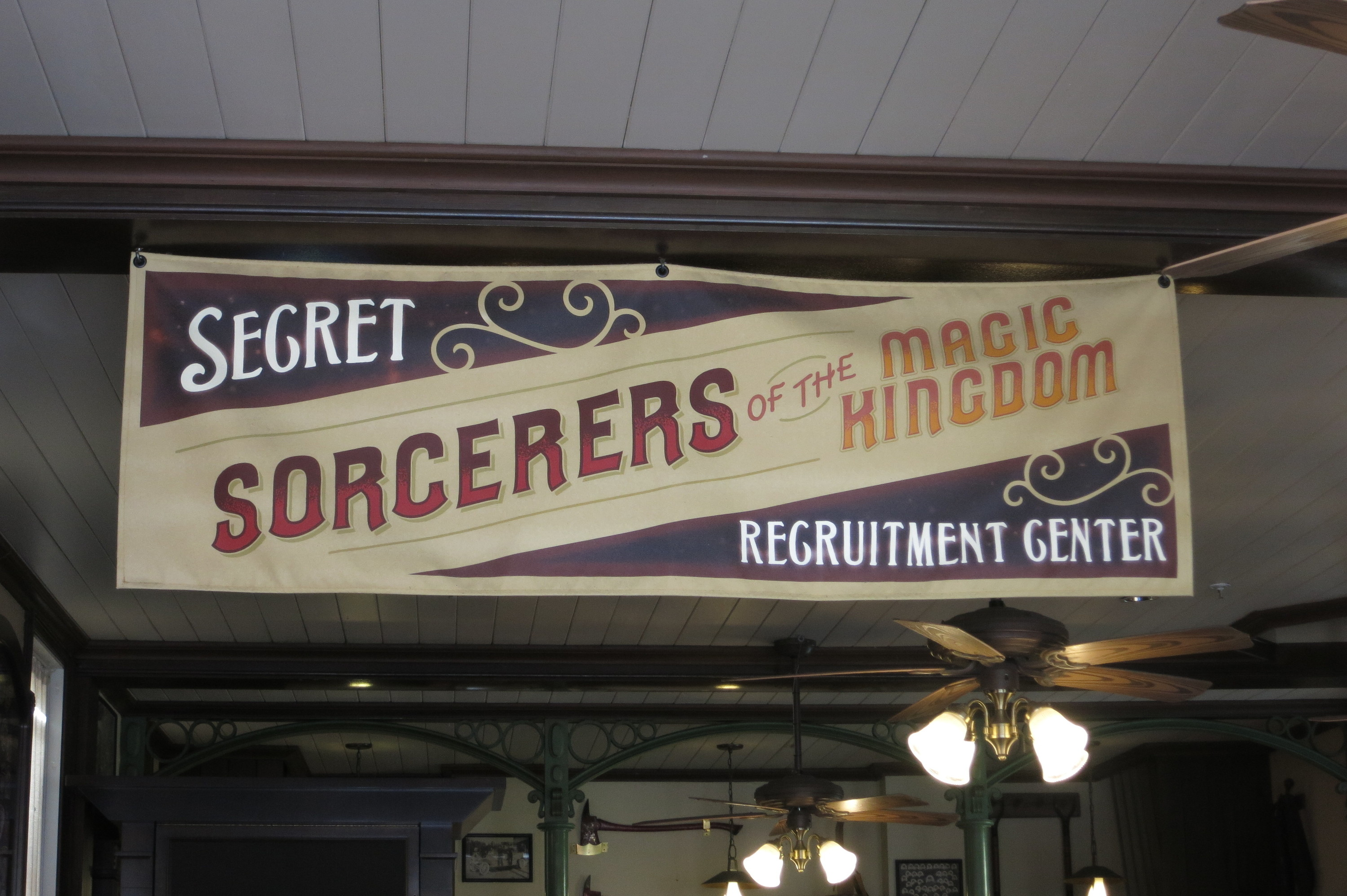 A large banner hanging from a wooden beam, with stylized font reading 'Secret Sorcerers of the Magic Kingdom Recruitment Center'. Beyond it is a cozy, rustic interior, with light fixings on the ceiling that have wooden fan blades attached.