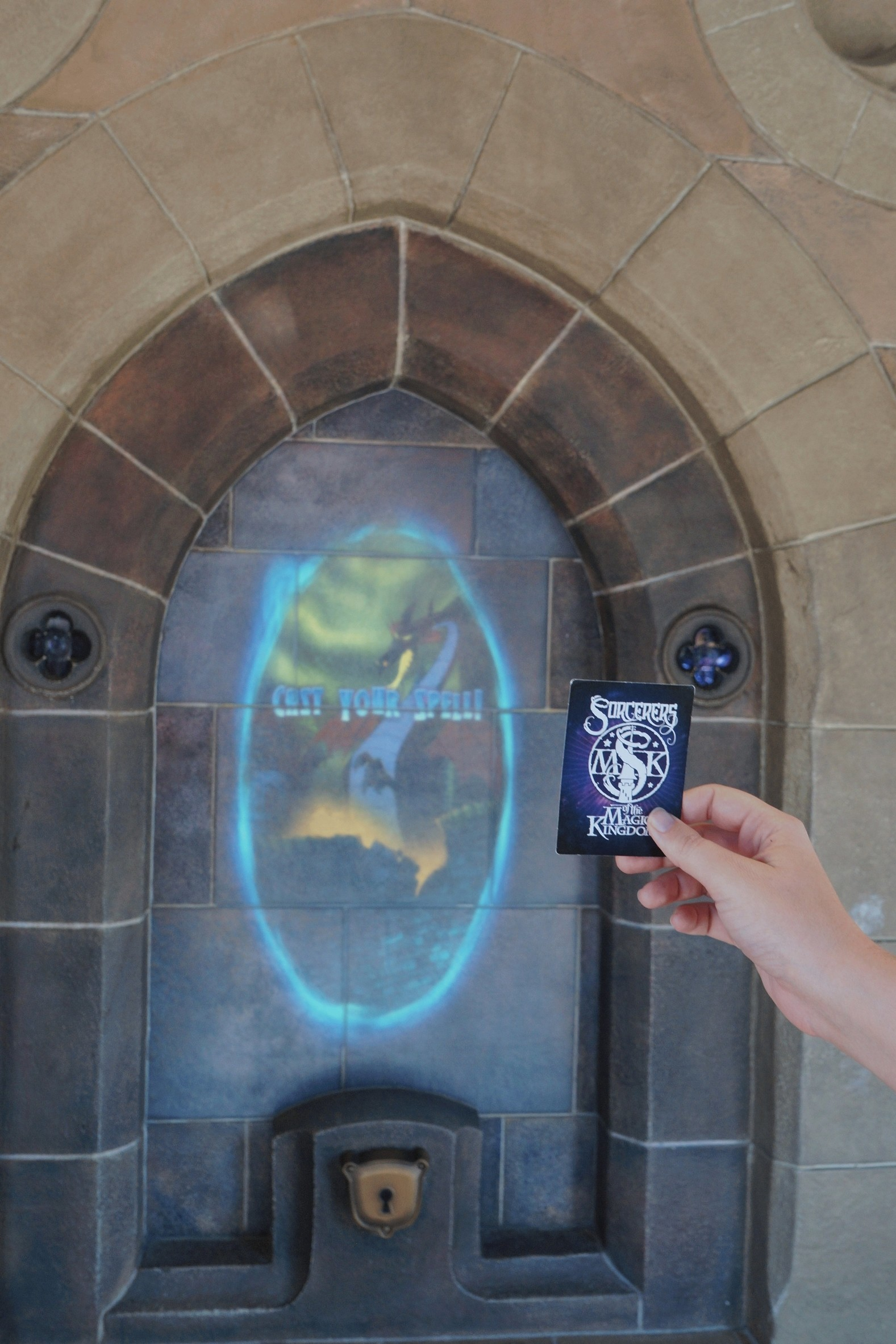 A hand holding up a card with a Sorcerers of the Magic Kingdom logo on the back, which is facing the camera. It is being held up to a kind of window inset into a stone wall with a gold lock at the bottom, which shows an animated picture of Maleficent in dragon form, with the words CAST YOUR SPELL written across it in blue. The image of Maleficent is encircled in the same bright blue colour, like a portal.